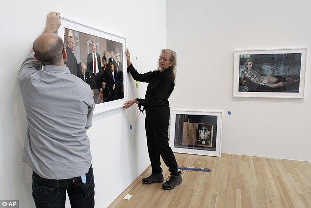 Presentation: Annie Leibovitz, right, helps Zak Kelley, of Columbus, hang one of her photographic prints containing President George W Bush and his cabinet members